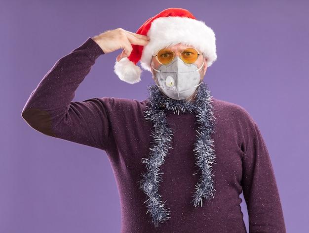 Сытый мужчина средних лет в шляпе санта-клауса и защитной маске с гирляндой из мишуры на шее в очках делает жест самоубийства, изолированный на фиолетовой стене