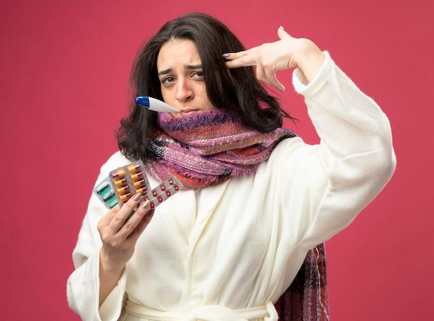 Stufo giovane ragazza caucasica malata che indossa veste e sciarpa che tiene confezioni di capsule mediche facendo gesto di suicidio con il termometro in bocca isolato sulla parete cremisi