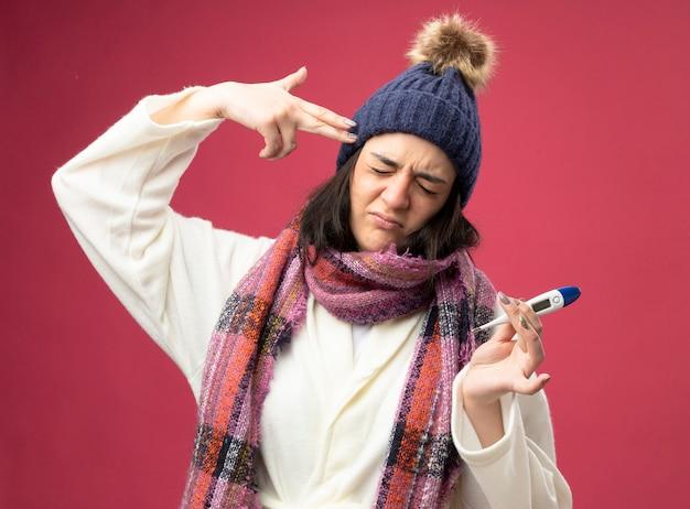 Stufo di giovane ragazza malata caucasica che indossa un cappello invernale di veste e sciarpa che tiene il termometro che fa gesto di suicidio con gli occhi chiusi isolati sulla parete cremisi