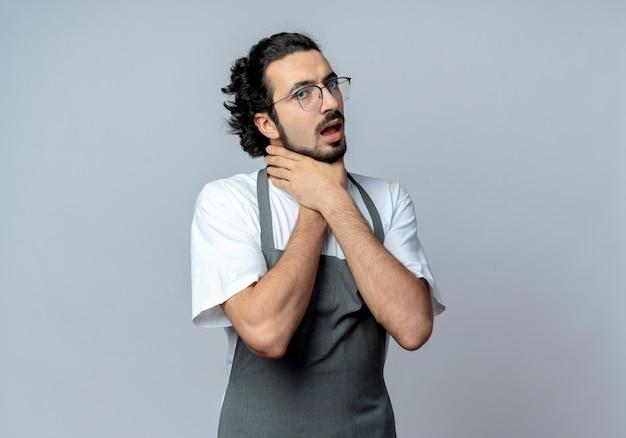 Stufo giovane barbiere maschio caucasico con gli occhiali e fascia per capelli ondulati in uniforme che si soffoca isolato su sfondo bianco con copia spazio