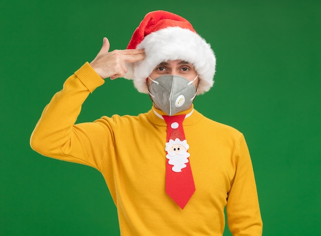 Fed up young caucasian man wearing christmas hat and tie with protective mask looking at camera doing suicide gesture isolated on green background
