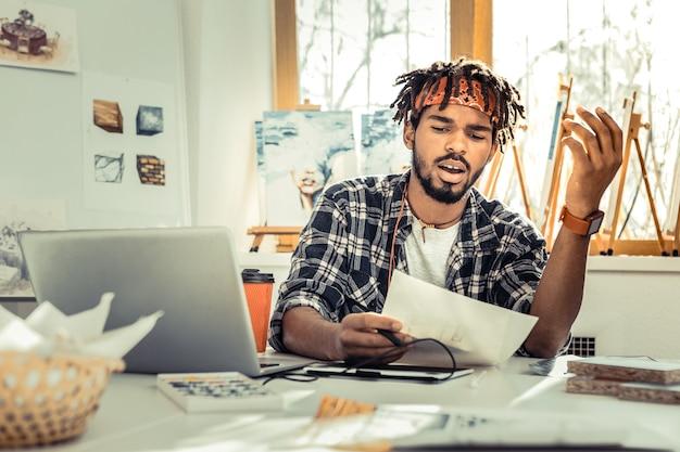 うんざり。一日中働いている間、ドレッドヘアがうんざりしていると感じている若い創造的なアーティスト