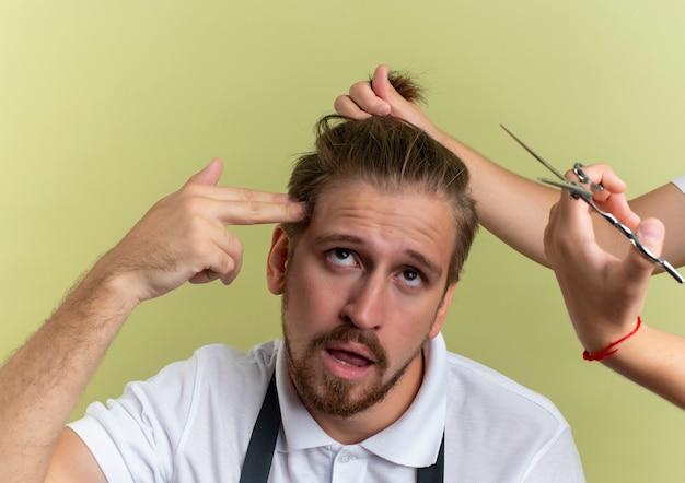 Stufo giovane bel barbiere gesticolando suicidio alzando lo sguardo con qualcuno che tiene e si prepara a tagliargli i capelli isolato su verde oliva