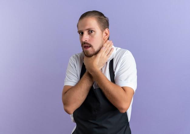 Stufo giovane barbiere bello che indossa l'uniforme facendo gesto di suicidio cercando di soffocare se stesso isolato su viola con copia spazio
