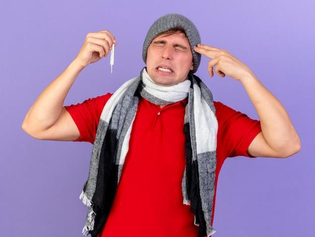 冬の帽子とスカーフを身に着けている若いハンサムな金髪の病気の人にうんざりして、紫色の壁に隔離された目を閉じて自殺ジェスチャーをしている温度計を保持しています