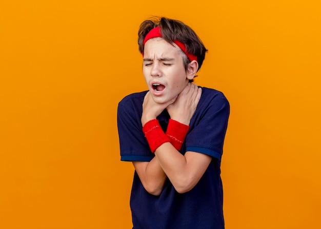 Stufo giovane ragazzo sportivo bello che indossa fascia e braccialetti con apparecchi ortodontici mantenendo le mani incrociate soffocandosi con gli occhi chiusi isolati sulla parete arancione