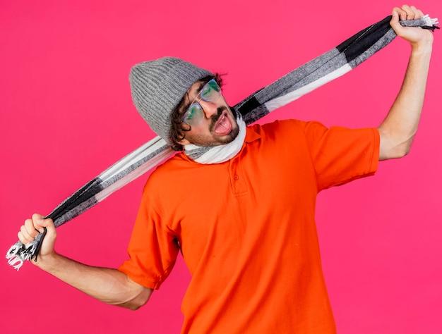 분홍색 벽에 고립 된 스카프로 자신을 질식시키는 안경 겨울 모자와 스카프를 착용하는 젊은 아픈 남자를 지쳤다.