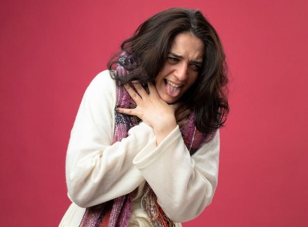 분홍색 벽에 고립 된 자신을 질식하는 측면을보고 가운과 스카프를 착용하는 젊은 아픈 여자를 지쳤다.