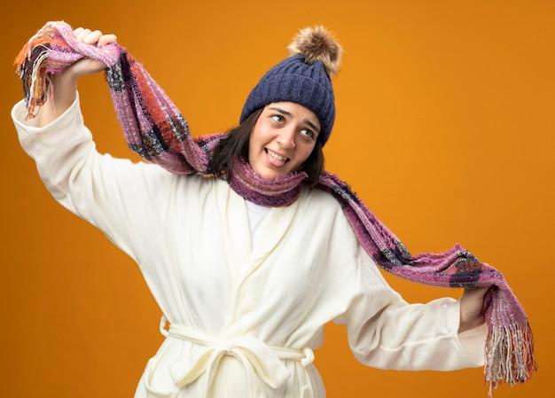 Stufo di giovane donna malata che indossa un abito invernale cappello e sciarpa alzando lo sguardo facendo gesto di suicidio isolato sulla parete arancione