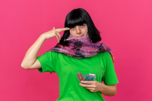 Stufo di giovane donna malata che indossa sciarpa che tiene termometro in bocca e pillole mediche guardando davanti facendo gesto di suicidio isolato sulla parete rosa