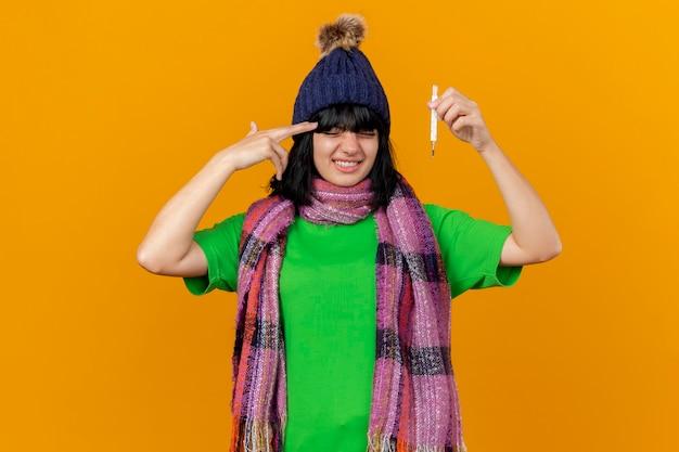 Сытая по горло молодая больная женщина в зимней шапке и шарфе с термометром делает жест самоубийства, изолированное на оранжевой стене