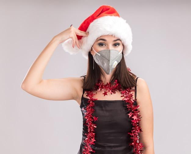 흰색 배경에 고립 된 자살 제스처를 하 고 카메라를보고 목 주위에 산타 모자와 보호 마스크 반짝이 갈 랜드를 입고 젊은 예쁜 백인 여자를 저리