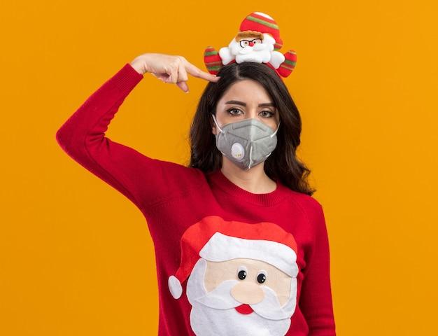 オレンジ色の壁に隔離された自殺ジェスチャーを行う保護マスクとサンタクロースのヘッドバンドとセーターを着てうんざりした若いかわいい女の子