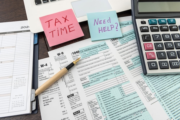 Federal 1040 tax form with sticker, calculator and pen. financical documents.