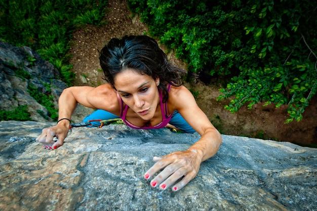 美しい少女の岩の上を登る料金