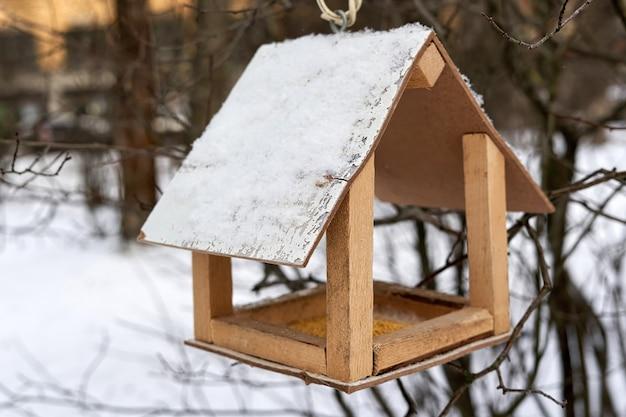 Кормушка с посыпанной крупой для кормления птиц зимой