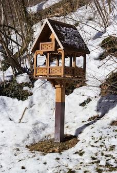 雪に覆われた公園の鳥の餌箱
