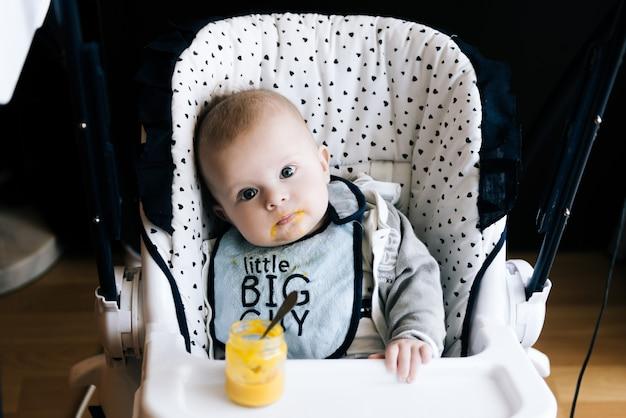 Кормление. прелестный ребенок ребенок ест с ложкой в высоком стуле.