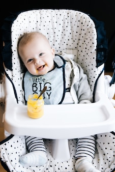 Feeding. adorable baby child eating with a spoon in high chair. baby