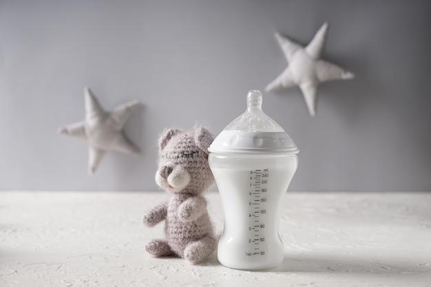 Бутылочка для кормления детской смесью с игрушкой плюшевого мишки на белом столе