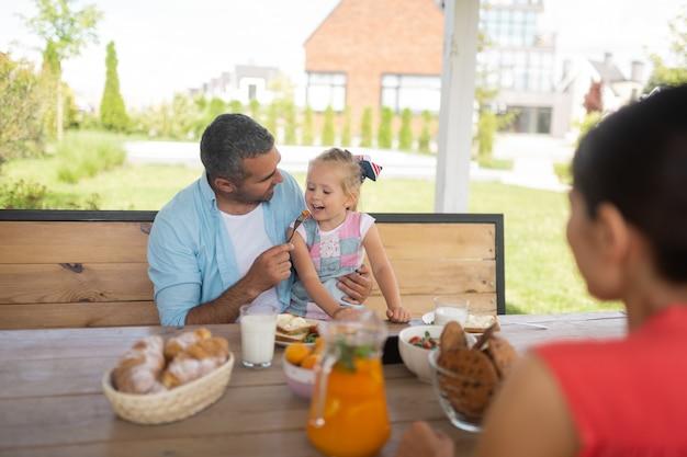 娘に餌をやる。外で朝食を楽しみながら彼の娘を養う思いやりのある愛情のあるパパ