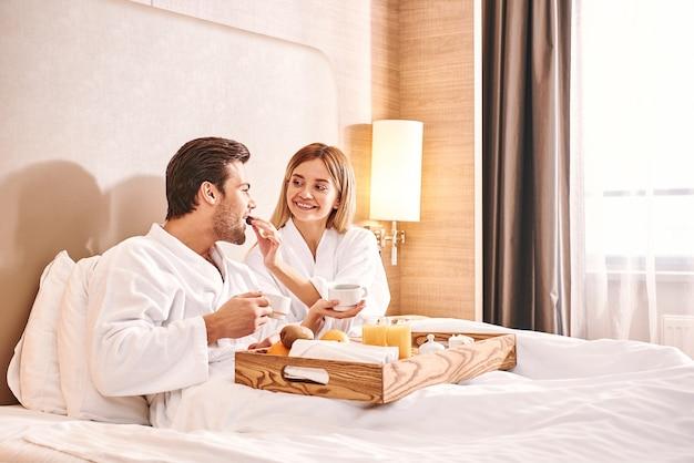 お互いに餌をやる。カップルはホテルの部屋のベッドで一緒に食事をしています。ラブストーリー。