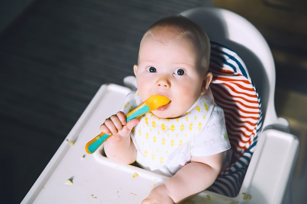 Feeding messy smiling baby eating with a spoon in high chair babys first solid food