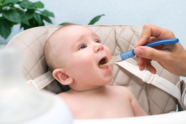 Кормление малыша. мама кормит ребенка овощным пюре ложкой. счастливый ребенок, сидящий на высоком стуле, пристегнутый