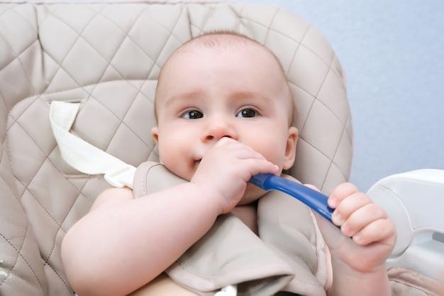 Кормление малыша. мама кормит ребенка овощным пюре ложкой. плачущий ребенок сидит на стульчике, пристегнутый. ребенок не хочет есть