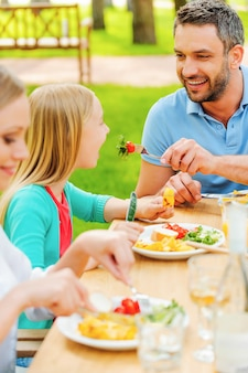 Feeding with fresh salad. happy young man feeding his daughter with salad while sitting together at the dining table outdoors
