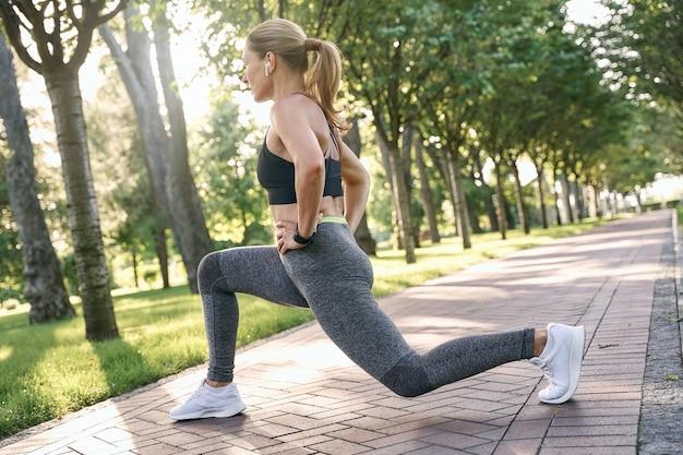 운동복을 입은 스포티한 중년 여성이 다리를 쭉 뻗고 있는 동안 집중적으로 보입니다.
