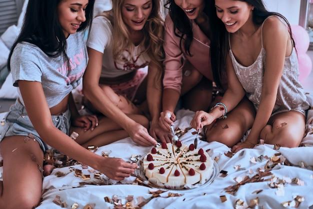 인생을 마음껏 즐겨라! 침실에서 파자마 파티를 하면서 케이크를 먹고 있는 잠옷을 입은 4명의 아름다운 젊은 여성