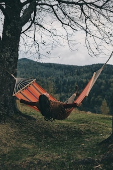 Feel the freedom.  beautiful young woman lying in hammock while relaxing on the valley under the tree