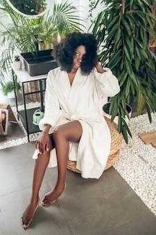 Feel good. beautiful dark-skinned woman in na bath robe looking enjoyed and pleased