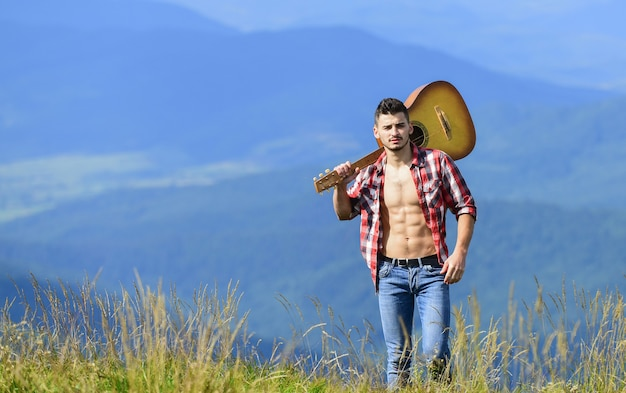 Feel good. hipster fashion. western camping and hiking. happy and free. cowboy man with bare muscular torso. acoustic guitar player. country music song. sexy man with guitar in checkered shirt.