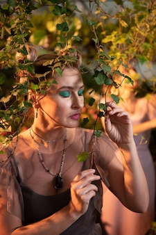 Почувствуйте энергию. красивая мирная женщина, стоя с закрытыми глазами, держа ветку дерева