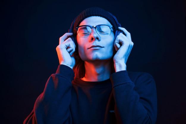 Чувствовать музыку. студия снята в темной студии с неоновым светом. портрет серьезного мужчины.