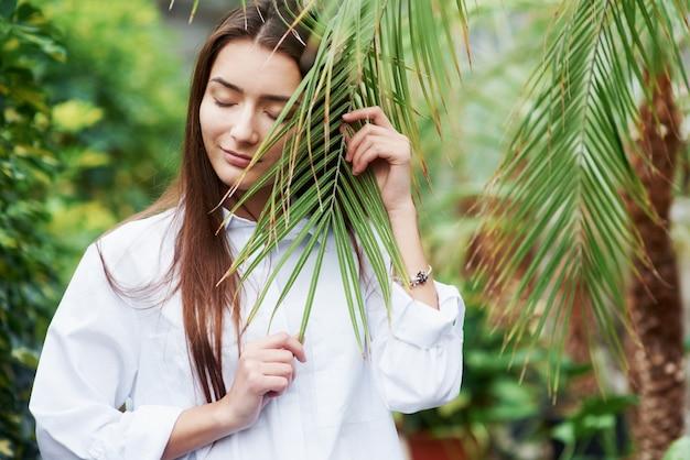 自然を感じてください。温室で枝を持っているゴージャスな若い女性。
