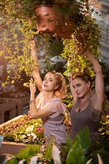 Почувствуйте природу. приятные привлекательные женщины, стоящие вместе среди растений, чувствуя природу