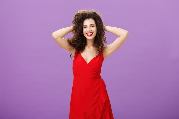 ショーの女王のように生き生きと元気になっている感じ。髪で遊んで、紫色の壁の上の新しい衣装で美しく感じて広く笑っているスタイリッシュな赤いイブニングドレスののんきなエレガントな縮れ毛の女性。