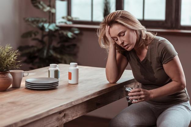 気持ち悪い。パニック発作後に発汗し、気分が落ち込んでいるストレスを感じて落ち込んでいる女性