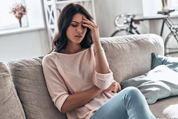 기분이 나쁘다. 집에서 소파에 앉아있는 동안 두통으로 고통받는 좌절 된 젊은 여성