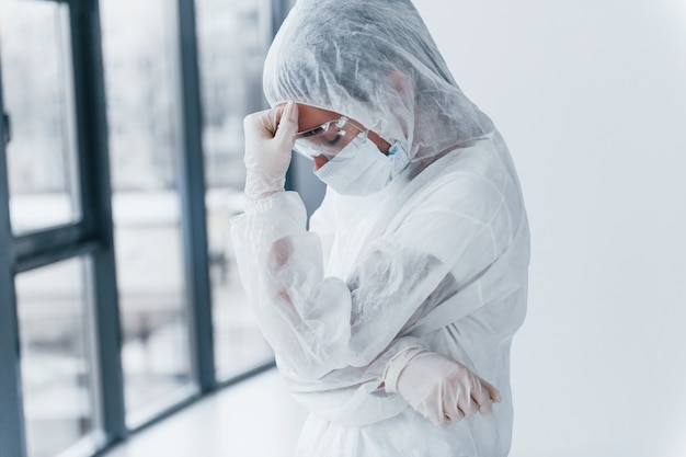 Feeling bad, tired and depressed. portrait of female doctor scientist in lab coat, defensive eyewear and mask