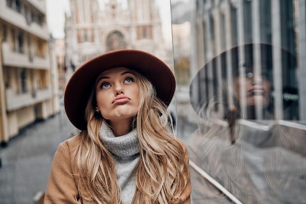 Скучно. привлекательная молодая женщина в шляпе и пальто корчит лицо и смотрит в сторону, проводя время в городе