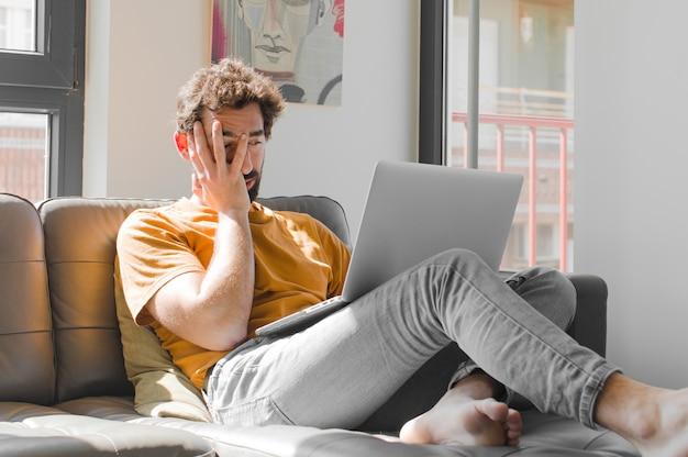 手で顔を抱える退屈で退屈な仕事の後、退屈な欲求不満と眠気を感じる