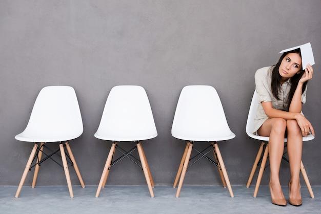 Мне скучно ждать. скучно молодая бизнес-леди держит бумагу на голове и смотрит в сторону, сидя на стуле на сером фоне