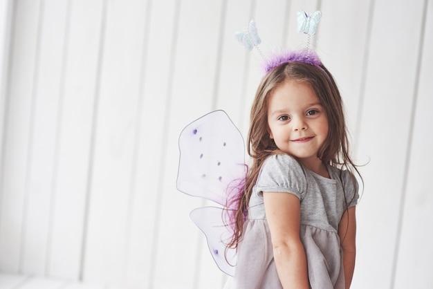 Чувство спокойствия и счастья. красивая маленькая девочка в костюме феи весело позирует для фотографий.