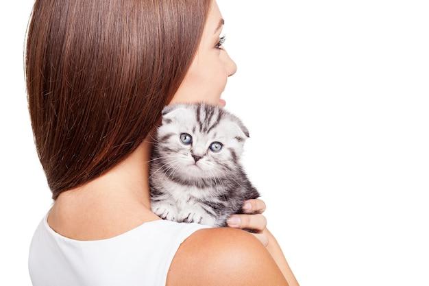Ощущение спокойствия и защищенности. красивая молодая женщина, несущая своего маленького котенка на плече и улыбаясь, стоя на белом фоне