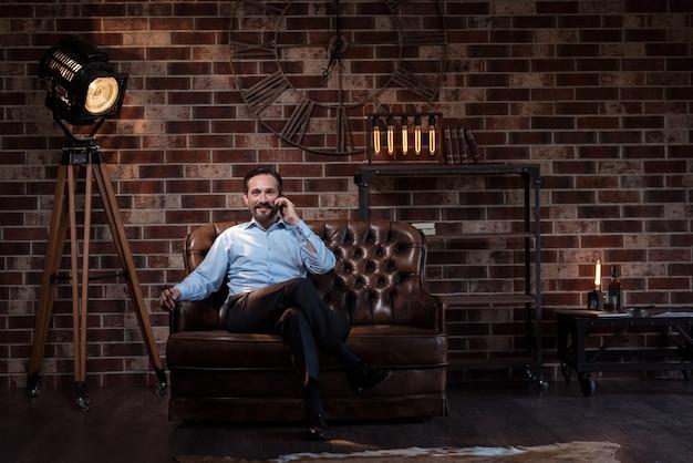 心地が良い。ソファに座って、彼の前を見ながら電話で話しているハンサムな楽しい自営業の男