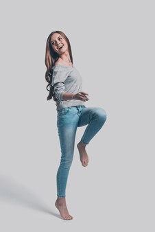 Чувствует себя комфортно в своем стиле. полнометражный студийный снимок привлекательной молодой женщины в повседневной одежде, прыгающей и выглядящей счастливой